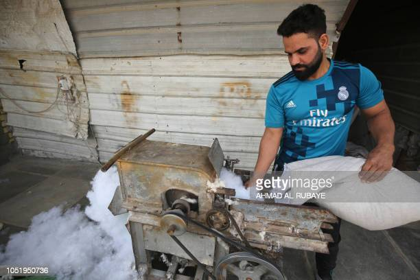 An Iraqi artisan carders cotton to make mattress at his workshop in Baghdad's mostly Shiite Sadr City district on October 12 2018