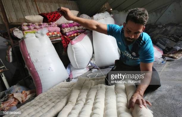 An Iraqi artisan sews a mattress at his workshop in Baghdad's mostly Shiite Sadr City district on October 12 2018