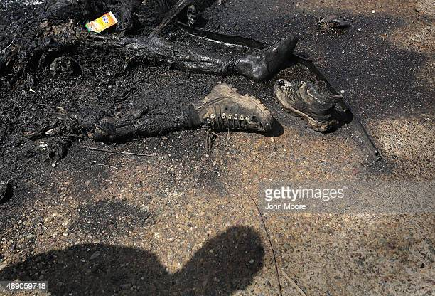 An Iraqi Badr Brigade militiaman looks over the charred remains of a suspected ISIS fighter on April 9 2015 in Tikrit Iraq Government troops and...