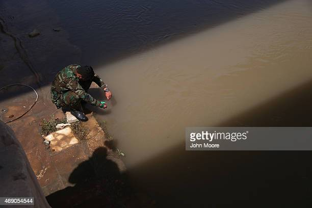 An Iraqi Badr Brigade militiaman mourns along the Tigris River in the palace compound of former Iraqi President Saddam Hussein on April 9 2015 in...
