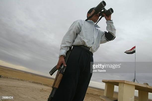 An Iraqi border guard looks through binoculars as he keeps an eye on the Iraqi/Syrian border October 31, 2003 just west of Sinjar, Iraq. U.S....
