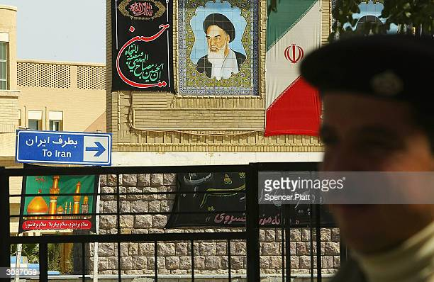 An Iraqi border guard stands in front of a picture of the late Iranian leader Ayatollah Khomeini which is displayed on the Iranian side March 15 2004...