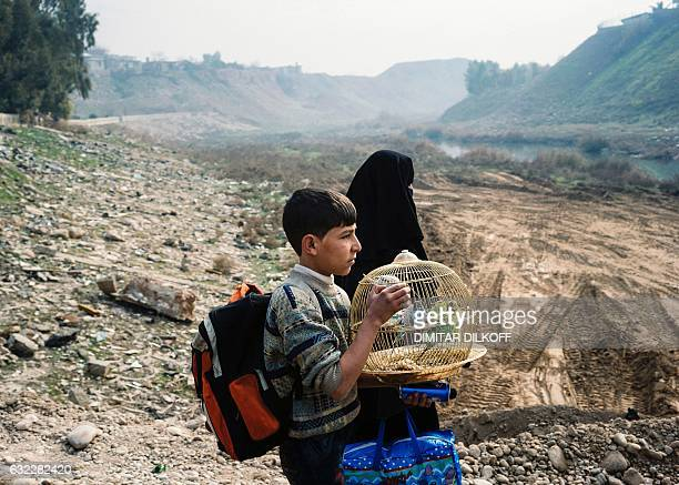 TOPSHOT An Iraqi boy carries a cage with songbirds as he walks on a makeshift river crossing next to a bridge which was destroyed by Islamic State...