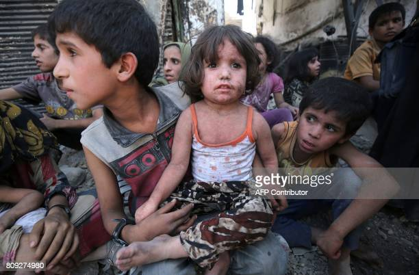An Iraqi boy carries a girl on his lap as he sits resting while fleeing from the Old City of Mosul on July 5 during the Iraqi government forces'...
