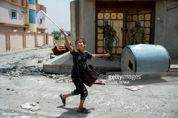 TOPSHOT An Iraqi boy carries a white flag as he evacuates his home as Iraqi forces advance in the northwestern alHaramat neighbourhood of Mosul on...