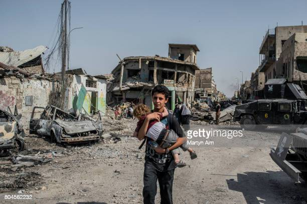 An Iraqi boy carries his sister through the Old City of west Mosul where heavy fighting continues on June 30 2017 in Mosul Iraq Iraqi forces continue...