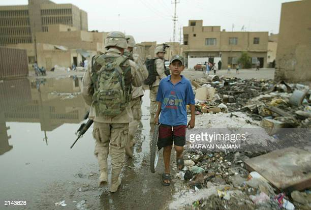 An Iraqi boy carrying a bicycle wheel walks past US soldiers from the 82nd Airborne Division patrolling the streets in northwest Baghdad 29 June...