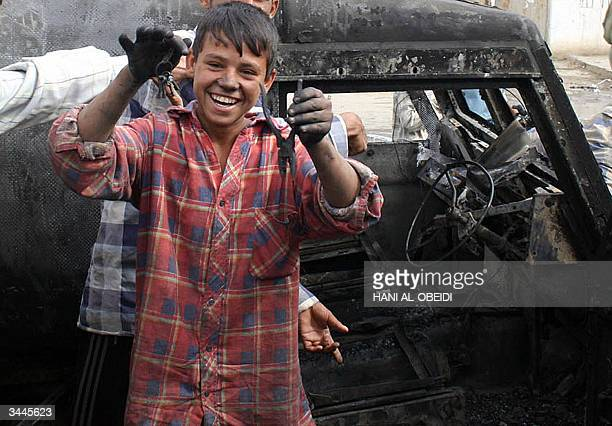 An Iraqi boy displays keys and a plier found in a wrecked British army armored vehicle in the southern city of Amara 19 April 2004 Clashes between...