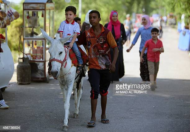 An Iraqi boy enjoys a pony ride at an amusement park during the Muslim holiday of Eid alAdha in the capital Baghdad on October 6 2014 The religious...