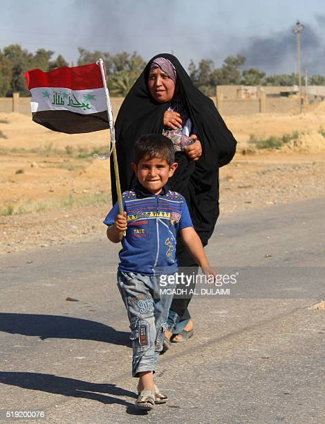 An Iraqi boy from the town of Heet in Iraq's Anbar province holds his national flag as government forces evacuate hundreds of civilians to a safe...