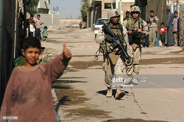 An Iraqi boy gives a thumbs up while US Marines of Fox Company 2nd Battalion 6th Marine Regiment pass during a patrol of the streets area November 13...