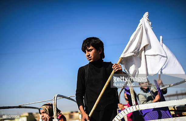 An Iraqi boy holding a white flag stands on a truck heading to camps housing displaced people on November 4 near the village of Gogjali on the...
