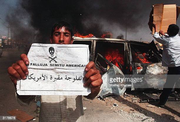 An Iraqi boy holds a sign that reads 'Fallujah is the cemetary of the Americans' as a sport utility vehicle burns behind him following an attack on...