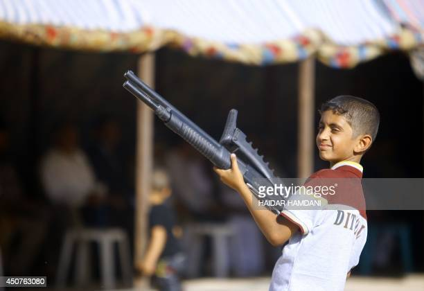 An Iraqi boy holds a weapon as he takes part in a gathering by Shiite tribesman to show their willingness to join Iraqi security forces in the fight...