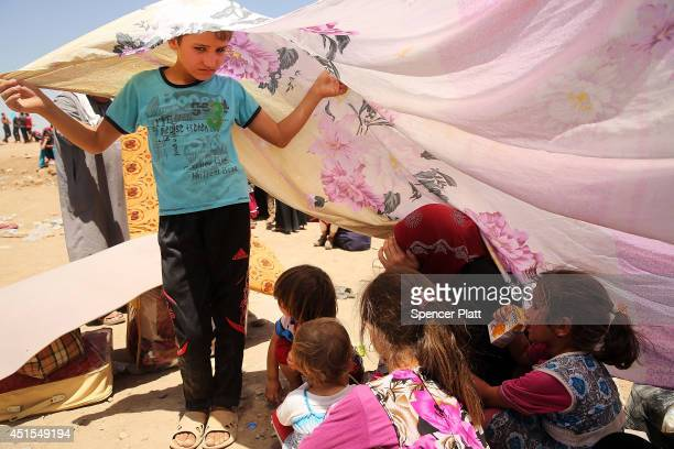 An Iraqi boy holds up a sheet to block the sun over his mother and sisters as over 1000 Iraqis who have fled fighting in and around the city of Mosul...