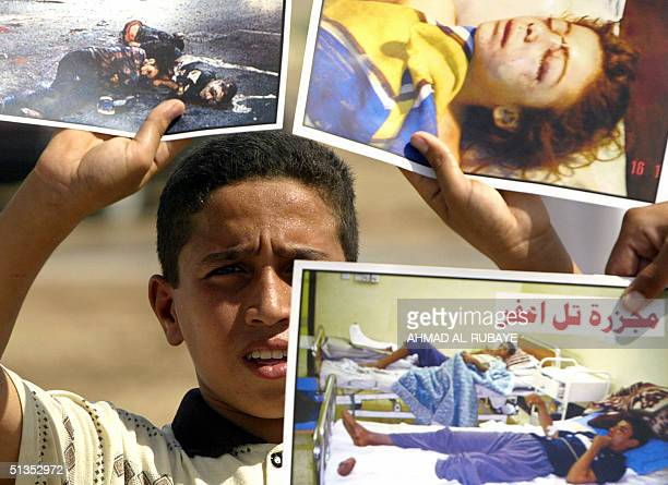 An Iraqi boy holds up pictures of victims of US assaults is Iraqi prior to a joint Shiite and Sunni Friday midday prayer outside the Abu Ghraib...