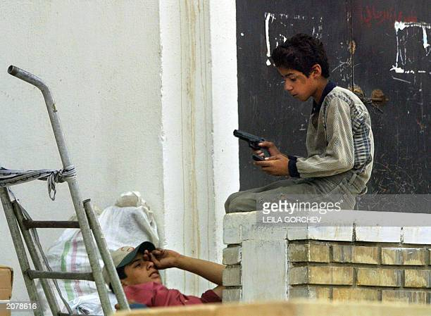 An Iraqi boy loads a handgun in the streets of Baghdad 02 June 2003 The USled administration has begun its twoweek countdown to the imposition of new...