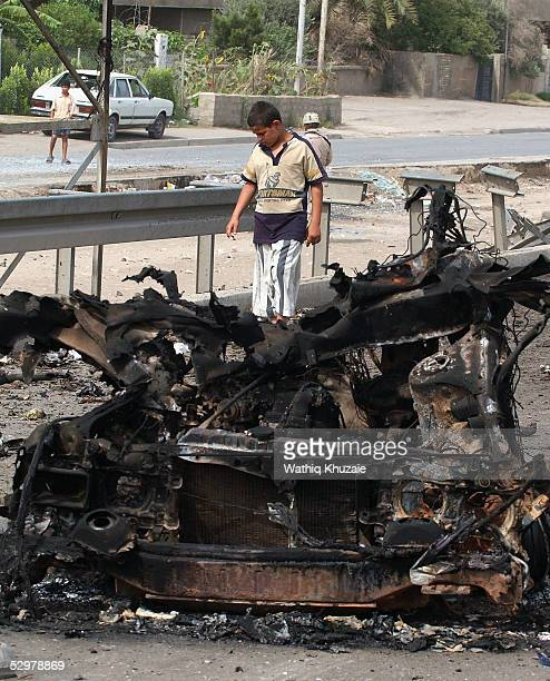 An Iraqi boy looks at a damaged car at the scene of a suicide car bomb explosion which failed to hit a US military convoy May 25 2005 in the area...