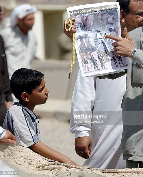 An Iraqi boy looks at a relative of an Iraqi prisoner being held by US authorities at the Abu Ghraib prison as he points at a newspaper featuring...