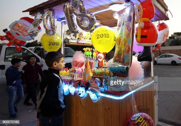 TOPSHOT An Iraqi boy looks at decoration items sold in the Shiite holy city of Najaf on December 31 on the last day of the year / AFP PHOTO /