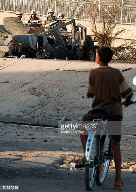 An Iraqi boy looks at US soldiers at the scene of a car bomb explosion September 21 2004 in Baghdad Iraq A car bomb exploded near a US military...