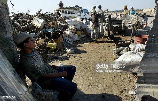 An Iraqi boy looks on as iraqi people deliver scarp metal and plastic to a recycling depot on November 21, 2004 in Baghdad, Iraq. A thriving...