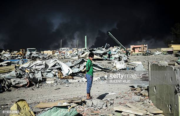 An Iraqi boy looks on as people collect wood and metal at a site which was targeted by an airstrike a couple of days ago in Qayyarah south of Mosul...