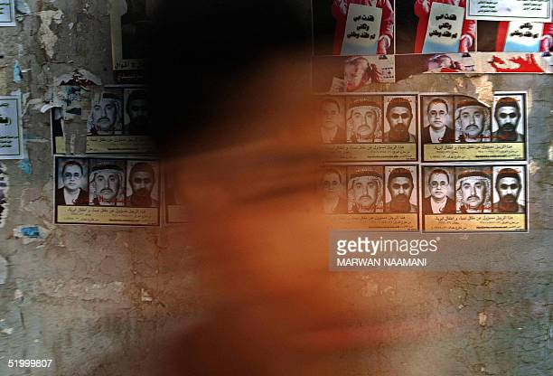 An Iraqi boy passes in front of posters of wanted Jordanian Islamist Abu Musab alZarqawi pasted on a wall in central Baghdad 16 January 2005...