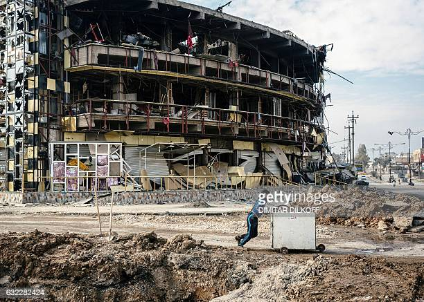 TOPSHOT An Iraqi boy pushes a cart with items down a street in front of a damaged building in eastern Mosul during the ongoing military operation...