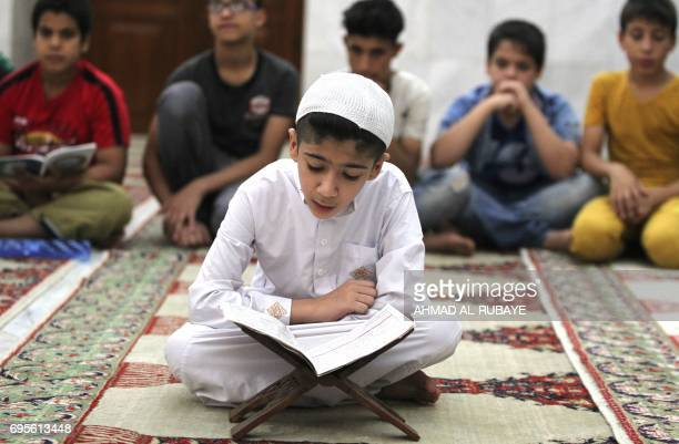 An Iraqi boy reads a copy of the Koran as he attends a reading class at the Sheikh Abdul Qadir aljailani mosque in central Baghdad on June 13 2016...