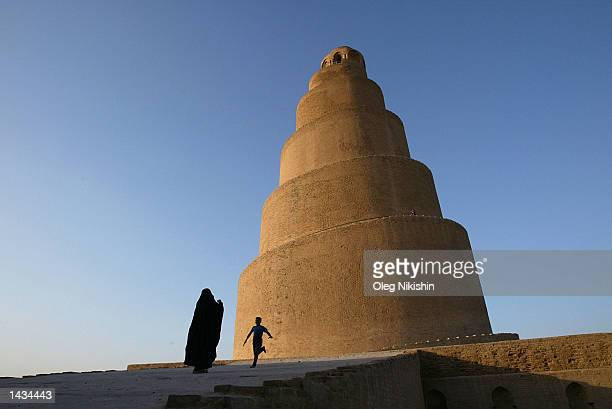 An Iraqi boy runs toward his mother in front of the XIX century spiral minaret September 25, 2002 in the town of Samara, 50 miles north of Bahgdad....