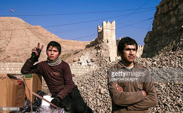 An Iraqi boy shows a Vsign by the walls of the Nineveh ruins in eastern Mosul on January 20 during the ongoing military operation against Islamic...