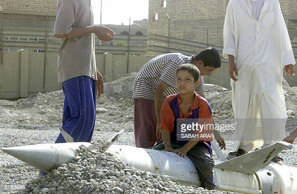 An Iraqi boy sits on a surfacetoair missile abandoned at a scrap yard in Baghdad as others watch 16 July 2003 An improvised explosive device exploded...