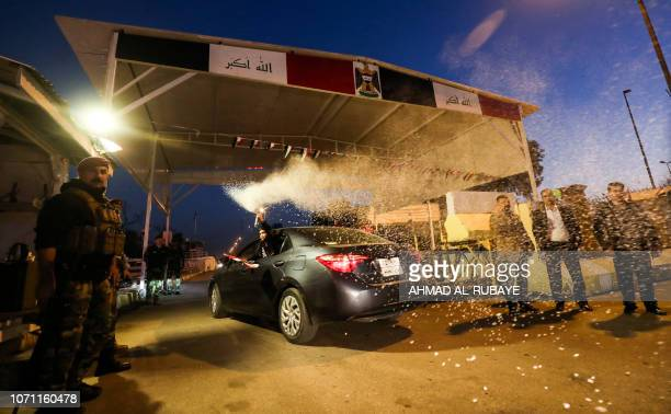An Iraqi boy sprays artificial snow from a canister as the car he is riding in passes through a security checkpoint of the capital Baghdad's...