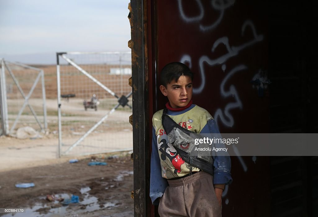 An Iraqi boy standing in front of a makeshift house at the Bahirka Refugee Camp where Christian families from Mosul's Hemdaniye town, Shabaks and Yazidis fled from the Daesh attacks, stay and battle the poor conditions.