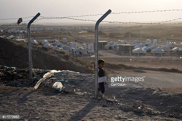 An Iraqi boy stands next to a post on a broken fence in Debaga refugee camp where people displaced by fighting in and around Mosul have sought...