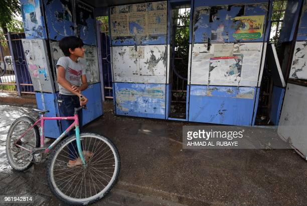 TOPSHOT An Iraqi boy stands walks past the site of an overnight suicide bomb attack in Baghdad's Shiite suburb of alShoala on May 24 2018 At least...