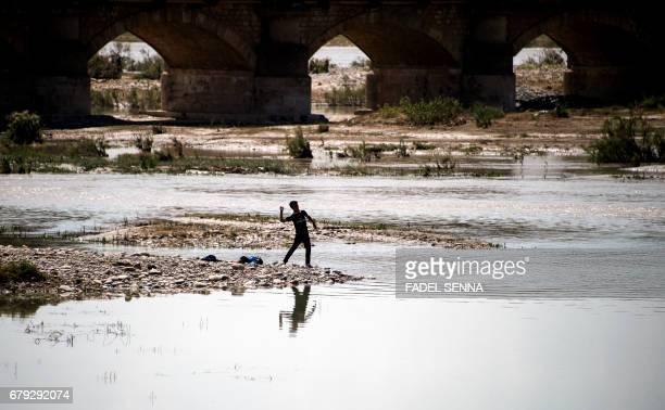 TOPSHOT An Iraqi boy throws a stone into a river near Arbil capital of the autonomous Kurdish region of northern Iraq on May 5 2017 / AFP PHOTO /...