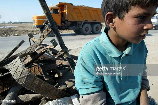 An Iraqi boy waits for a buyer to purchase his scarp metal and plastic on November 21, 2004 in Baghdad, Iraq. A thriving recycling industry has begun...