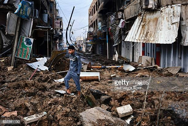 An Iraqi boy walks among debris on a street near Mosul's University on January 22 a week after Iraqi counter-terrorism service retook it from the...