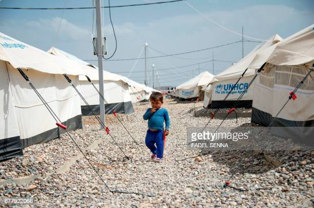 An Iraqi boy walks at a camp for internally displaced people in Hammam al-Alil after fleeing West Mosul due to the ongoing battles between government...