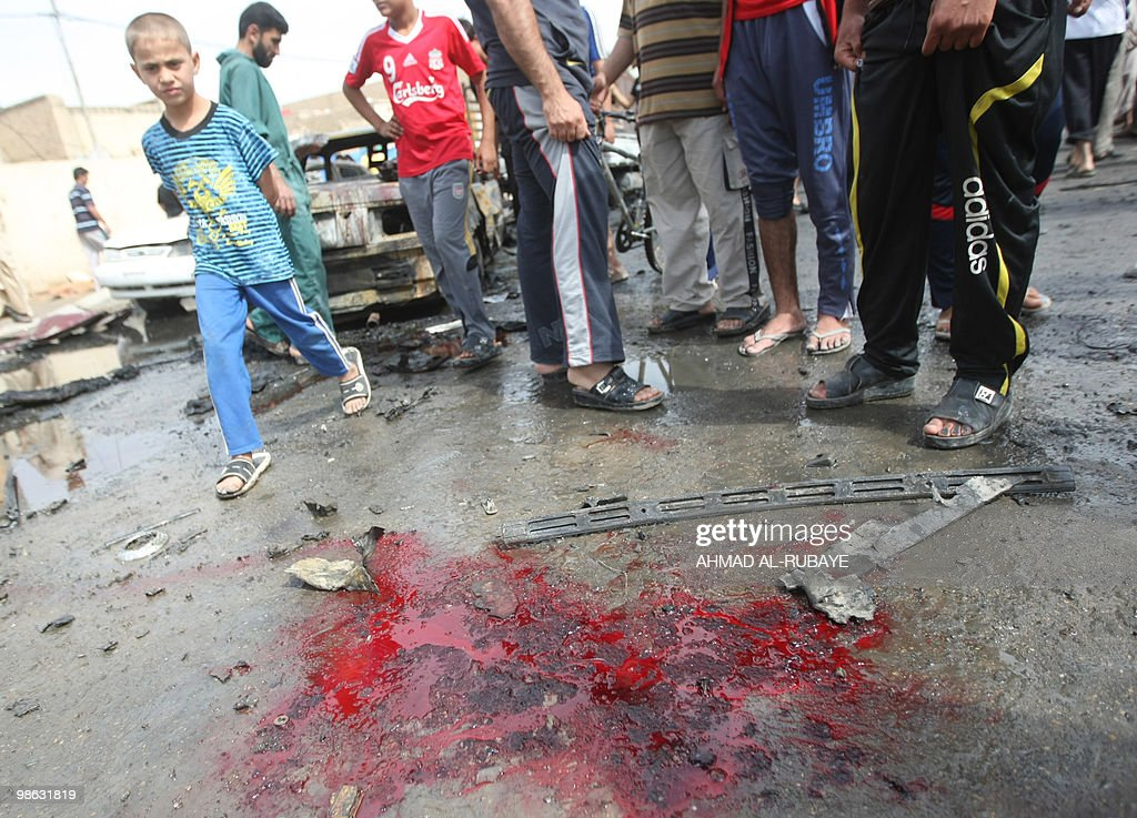 An iraqi boy walks by a pool of blood and debris from a car bomb explosion on April 23, 2010 in the impoverished Baghdad district of Sadr City. A series of five car bombs, three during prayers at Shiite mosques in Baghdad, and other attacks across Iraq killed 58 people, days after the government said Al-Qaeda was on the run.