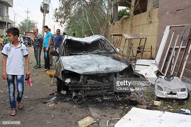 An Iraqi boy walks on May 10 2016 at the site of a car bomb explosion which hit the Shifta area in the city of Baquba the previous day killing at...