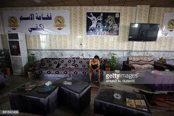 TOPSHOT An Iraqi boy walks past the blood stains and debris at a cafe that was popular with local fans of Spain's Real Madrid football club in the...