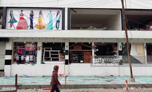 TOPSHOT An Iraqi boy walks past the damaged shop front of the alJawaher mall in eastern Baghdad the day after a bomb attack on January 12 2016...