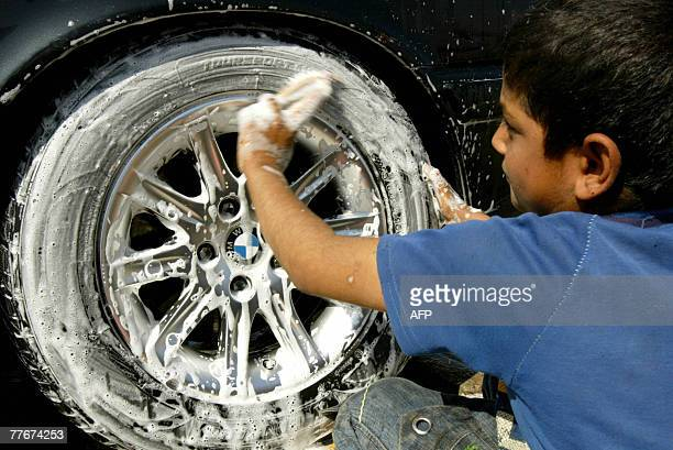 An Iraqi boy washes the tires of a car at a carwash station in central Baghdad 04 November 2007 Due to the violence in Iraq many children have left...