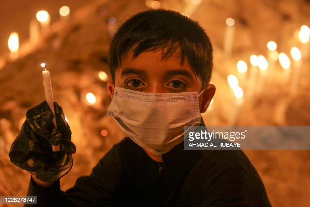 An Iraqi boy, wearing a protective face mask, carries a candle during a memorial ceremony on the tenth day of the month of Muharram which marks the...