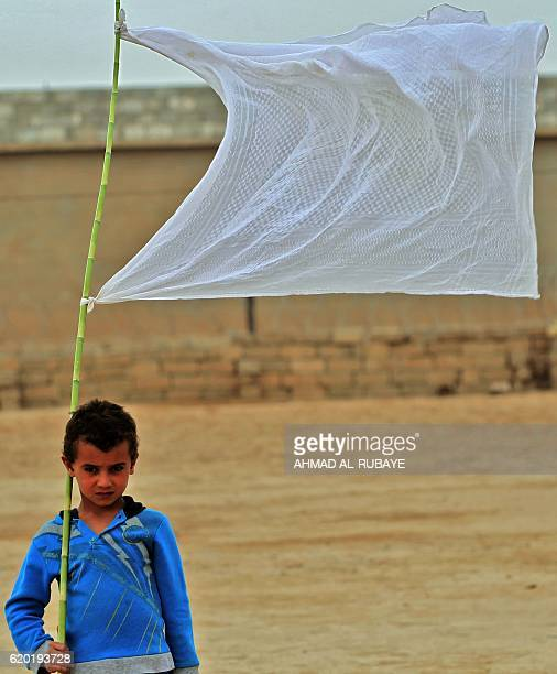 An Iraqi boy who was displaced from the village of Abu Shuwayhah south of the jihadistheld Mosul walks carrying a white flag as locals return to...