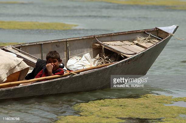 An Iraqi boys relaxes in a dug-out a his parents fish on the al-Huwaiza marshes northern Amara, 420 km south of Baghdad on June 13 considered to be...