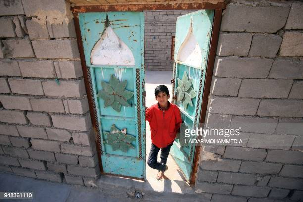 An Iraqi boys stands in the doorway of a house in alZubair south of Basra on February 11 2018 Informal housing settlements are flourishing in the...